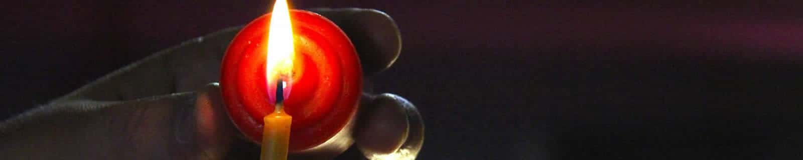 Hand holding a red votive candle